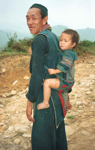 Black Hmong man carrying his granddaughter on his back in a baby carrier in the hills around Sa pa, Northern Vietnam 9510i28.jpg