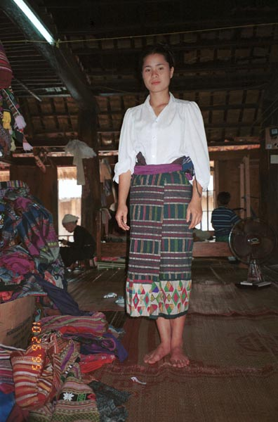 An old Thai minority woven sarong being modeled by a Thai girl in a village West of Hanoi, Vietnam.  The sarong is now in my collection.  See the old lady in the background winding bobbins ready for weaving.  In the foreground is a pile of woven lengths from various families in the village ready for sale. 9510A14E